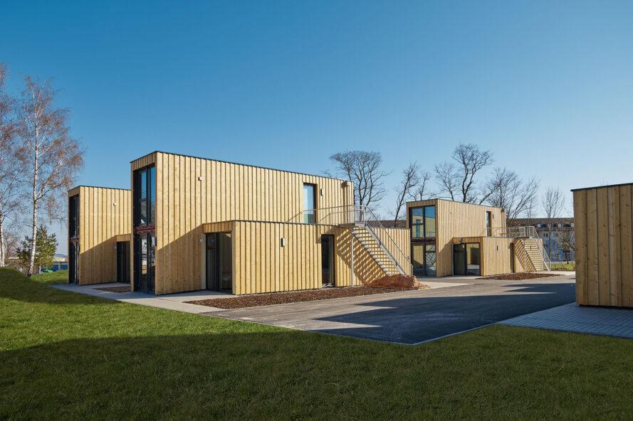 a grassy area surrounds several shipping container apartments covered in timber