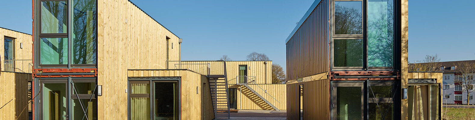 closeup of a line of shipping container micro-apartments covering in timber panels