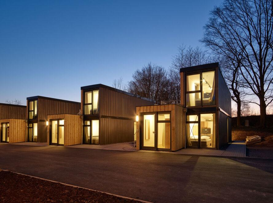 an evening shot of timber paneled micro-apartments lit up from within