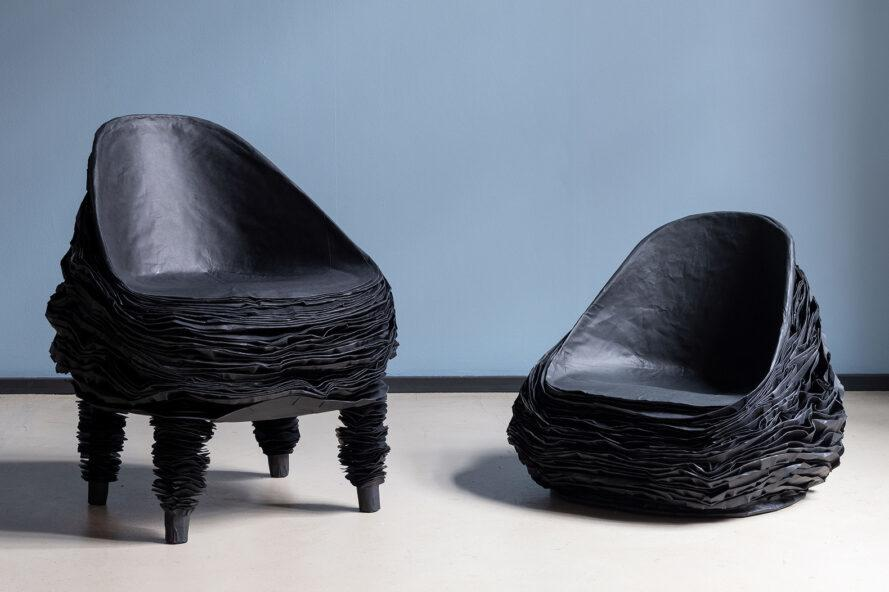 a black chair on legs to the left and a black chair without legs to the right. both stand against a blue background