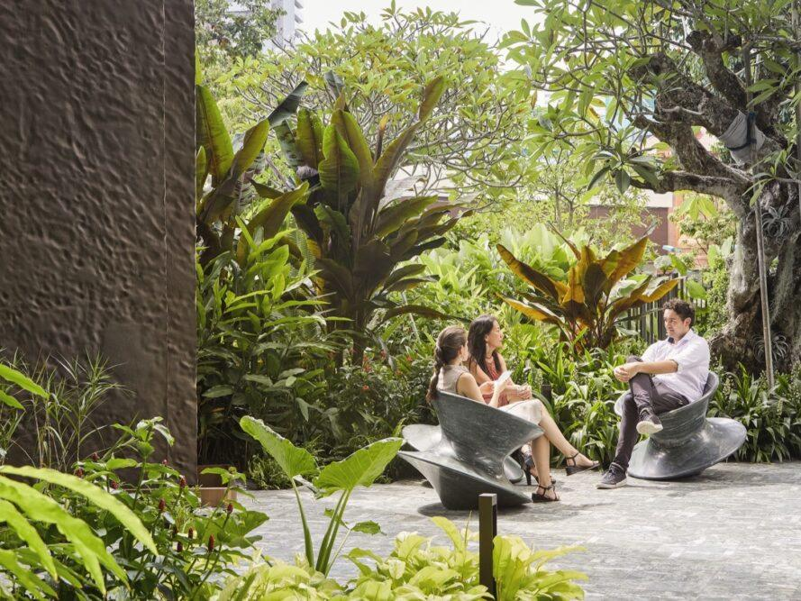 people sitting in gray spinning chairs in a lush courtyard