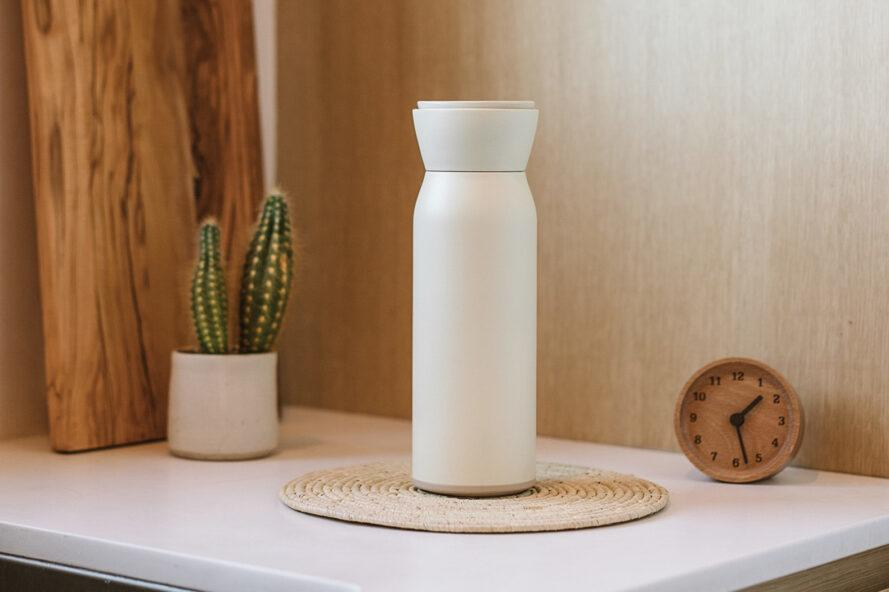 white reusable water bottle on a counter near wood cutting boards and a small plant