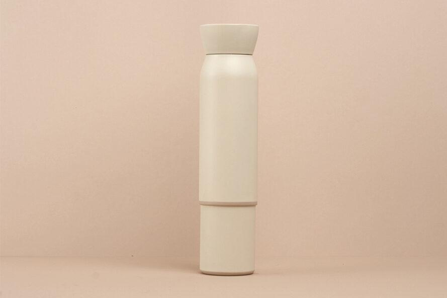 white reusable water bottle stacked on top of a small white coffee cup