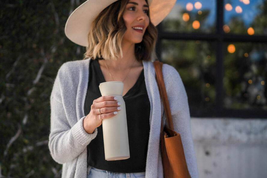 person carrying white reusable water bottle while on a walk