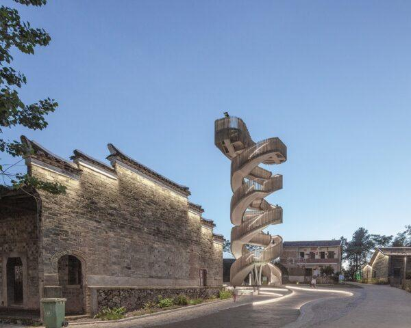 rendering of spiraling wood watchtower beside ancient stone building