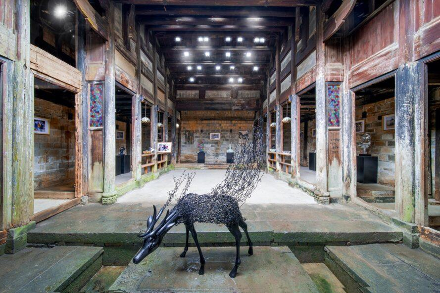 rendering of sculpture of an animal inside an old stone building