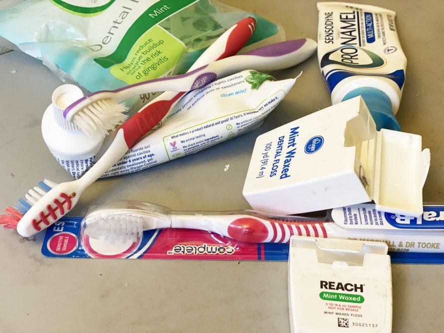 a pile of toothbrushes, toothpaste and floss containers and a bag of one-use floss instruments