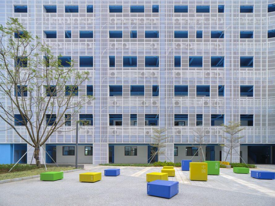 a school building with a courtyard in front of it. blue, yellow and green seating areas are placed throughout the courtyard