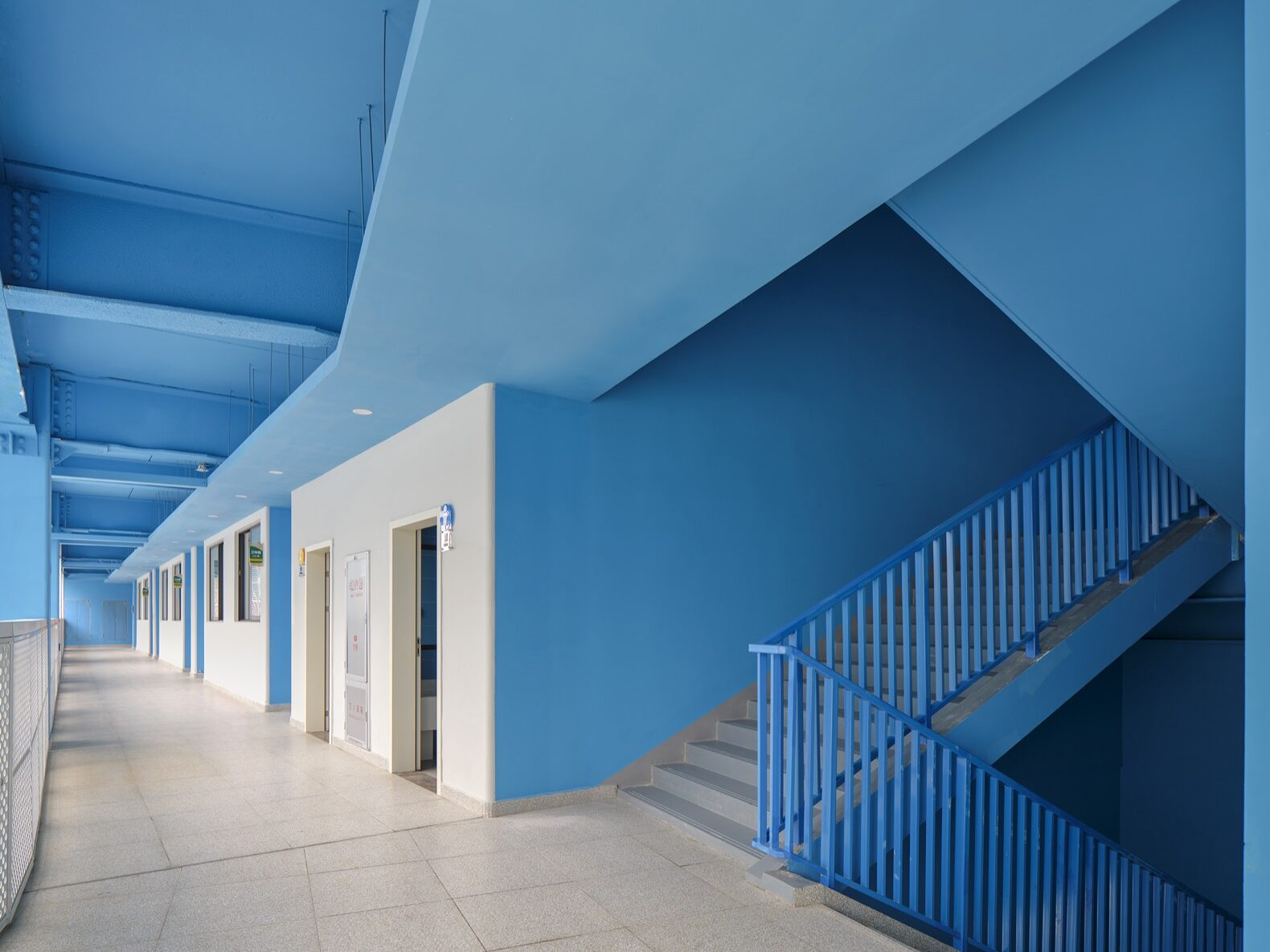 interior hallway of a school with blue walls and ceilings
