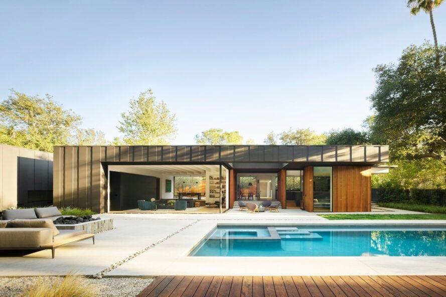 swimming pool and deck in front of one-story home