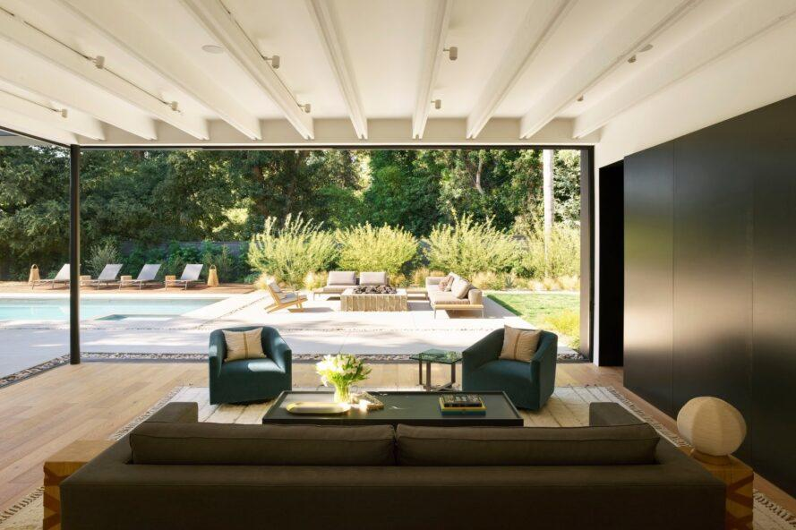 dark sofa and blue chairs near a glass wall open to a backyard