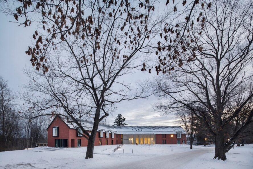 V-shaped, gabled brick building in snowy landscape