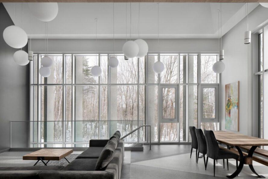 gray sofa beside wall of glass revealing a snowy landscape