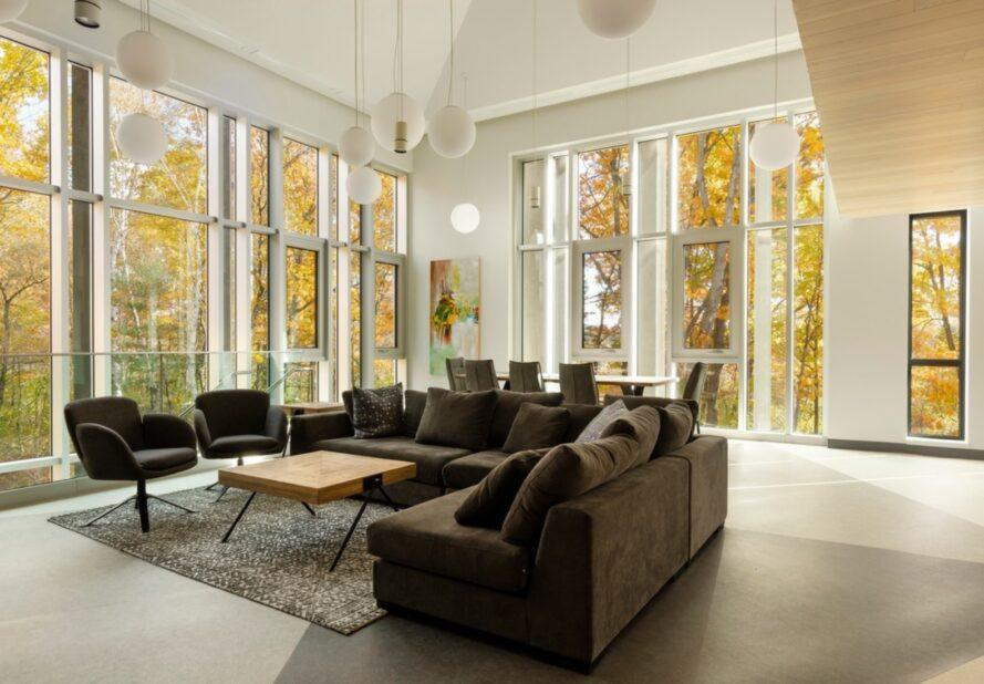 gray sectional sofa in white room with walls of windows revealing autumn leaves outside