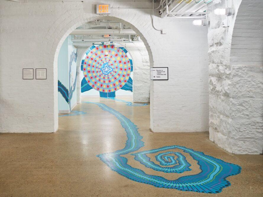 white room with arched doorways and playful blue mural on the floor
