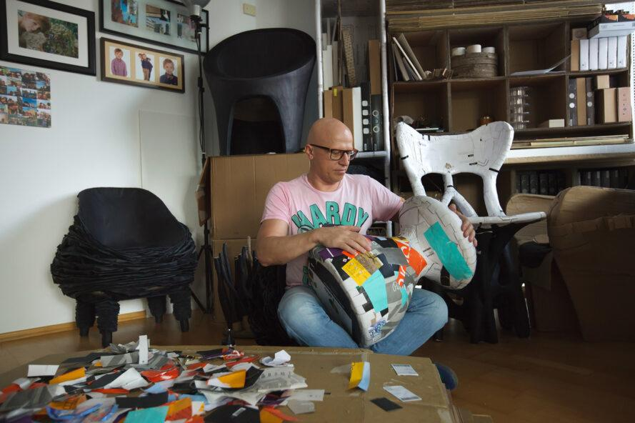 a man in a pink shirt surrounded by colorful paper as he works on creating a piece of furniture