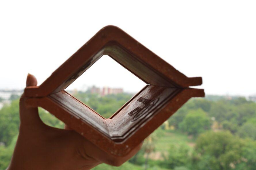 person holding two V-shaped clay tiles