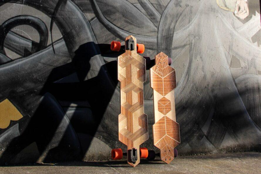 two wooden skateboards on black wall