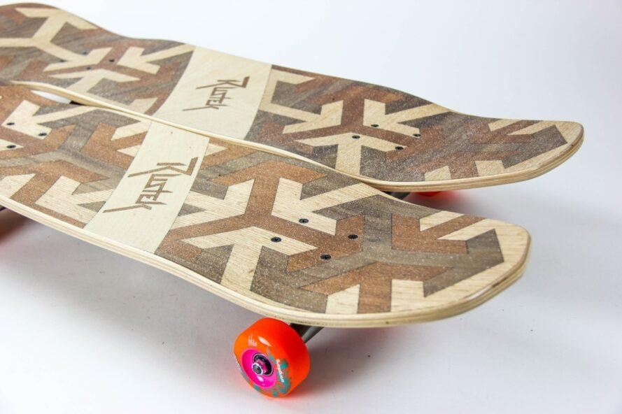 two wooden skateboards with orange wheels
