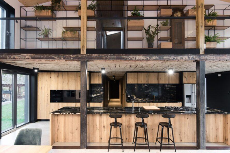 a view of the kitchen that shows the second floor above it. black accents and light-colored wood accents decorate the space