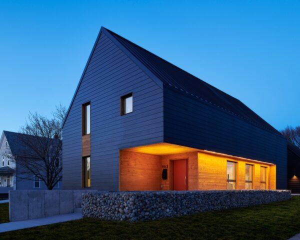 dark, gabled passive house with porch lights on at dusk