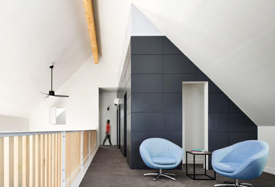 two blue lounge chairs on a lofted area