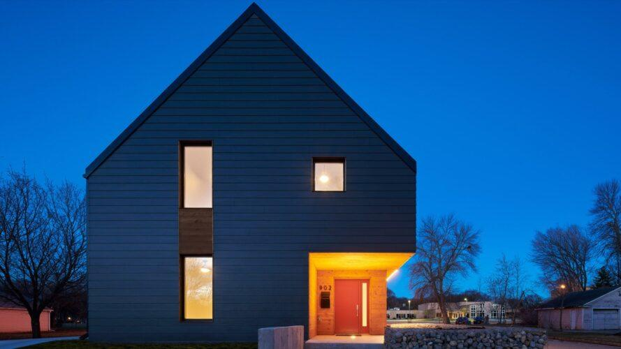 dark, gabled home with few windows lit up at dusk