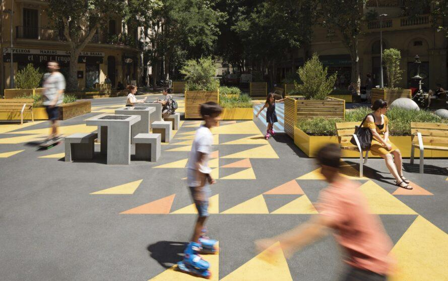 kids roller skating in a plaza with colorful floors and several planter boxes