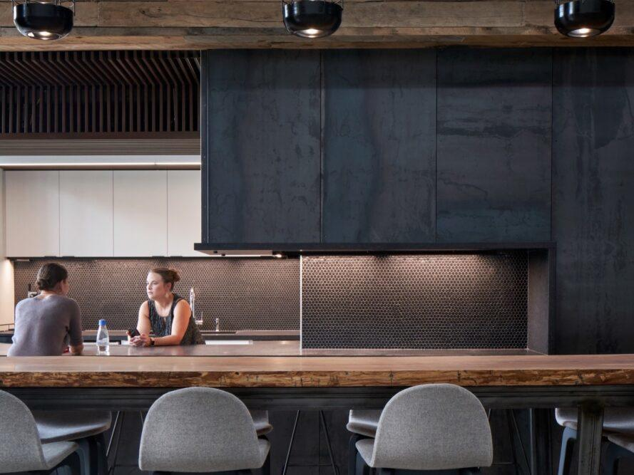 office kitchen with black walls, dark backsplash and wood counters