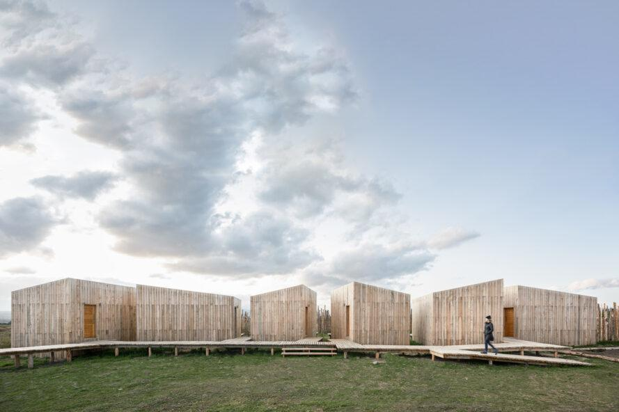 wood cabins with slanted roofs connected by winding wooden walkway