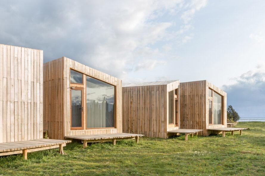wood cabins with slanted roofs and end walls made of glass