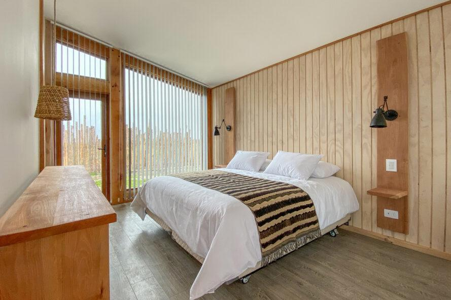 large white bed in wood-lined room with large windows