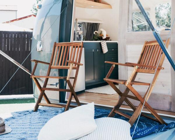 striped awning covering a fold-out deck with two wood chairs