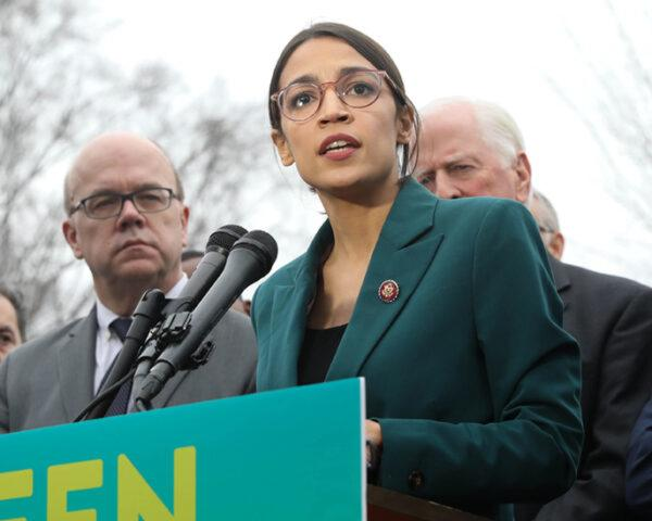Representative Alexandria Ocasio-Cortez standing at a podium with a sign that reads,