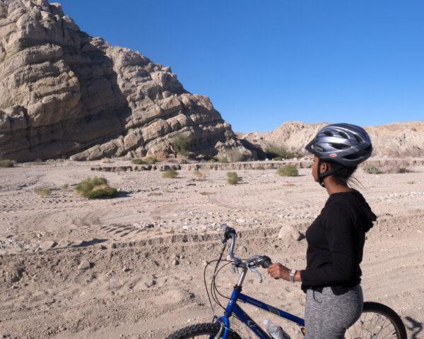 person on bike looking up at giant rock formation in the desert