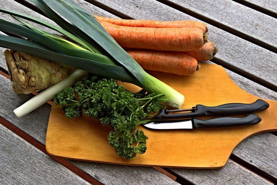 vegetables on a cutting board beside a knife and vegetable peeler