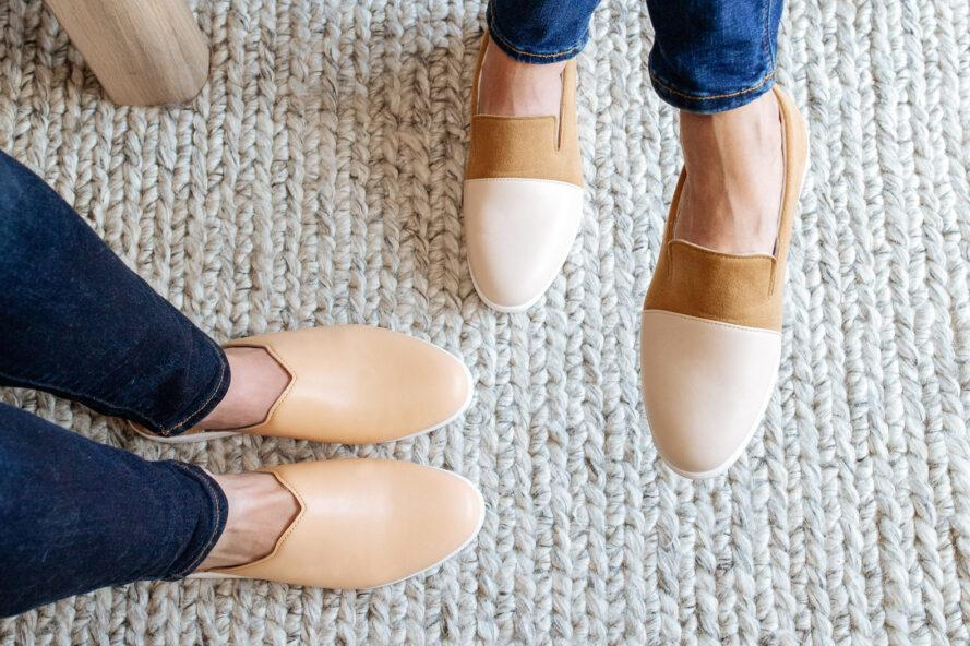 one person wearing tan mules and another person wearing two-tone tan loafers