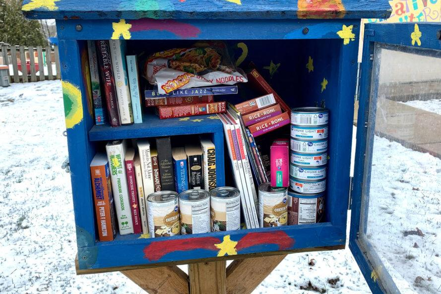 Little Free Library post filled with canned foods