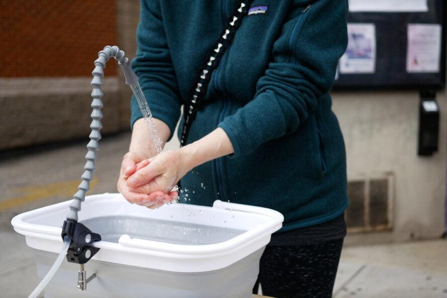 person washing hands in a portable sink