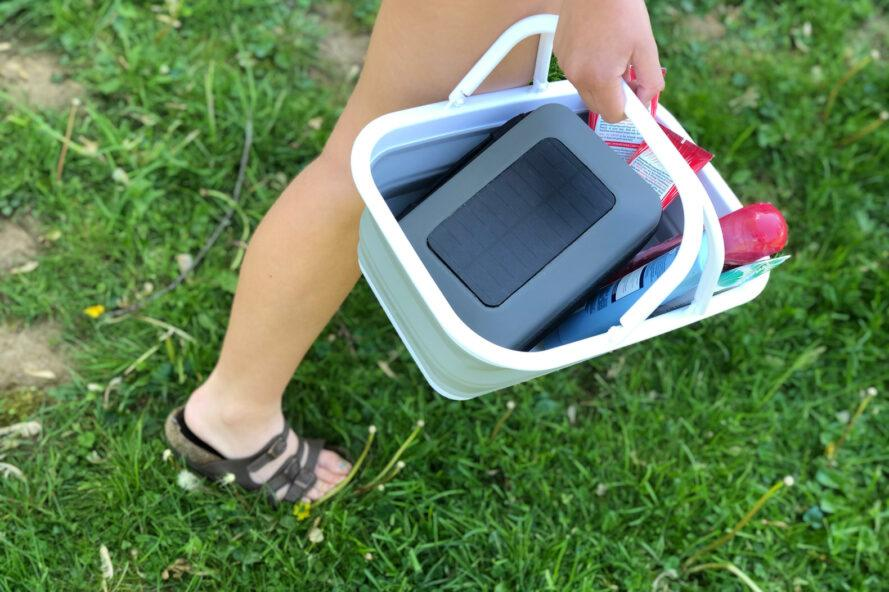 person carrying snacks and a solar charger in a portable, basket-like sink