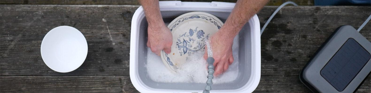 person washing dishes in a small, portable sink