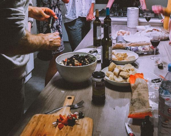 a group of people crowded around a kitchen counter filled with bowls of food, bags and bottles