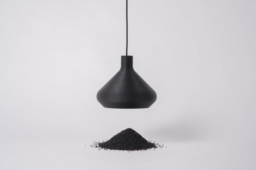 black pendant lamp hanging above small pile of black waste particles