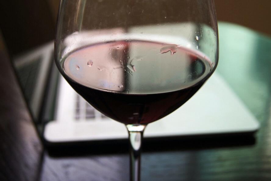 glass of red wine in front of a laptop