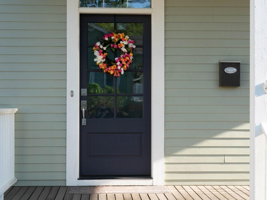 front door decorated with a tulip wreath