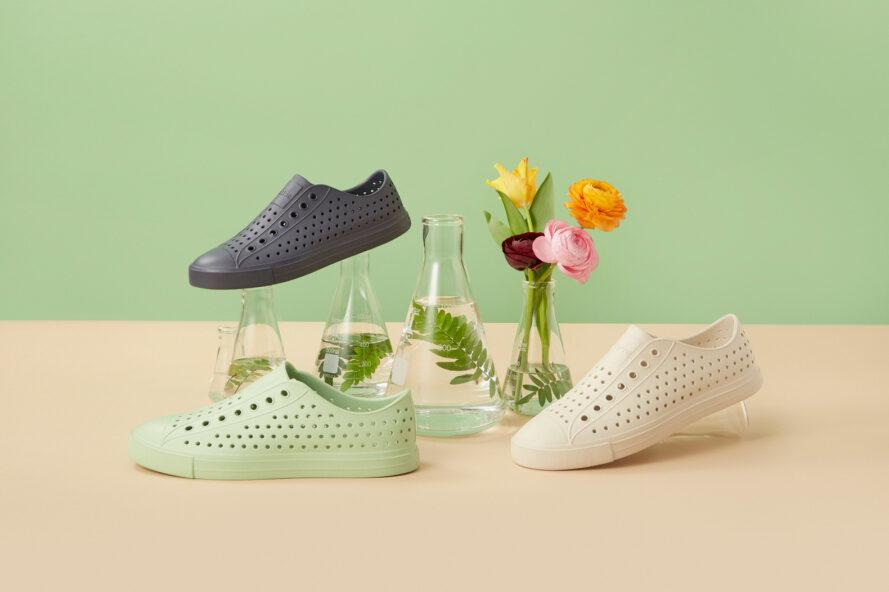 black, green and white perforated sneakers near vases of flowers