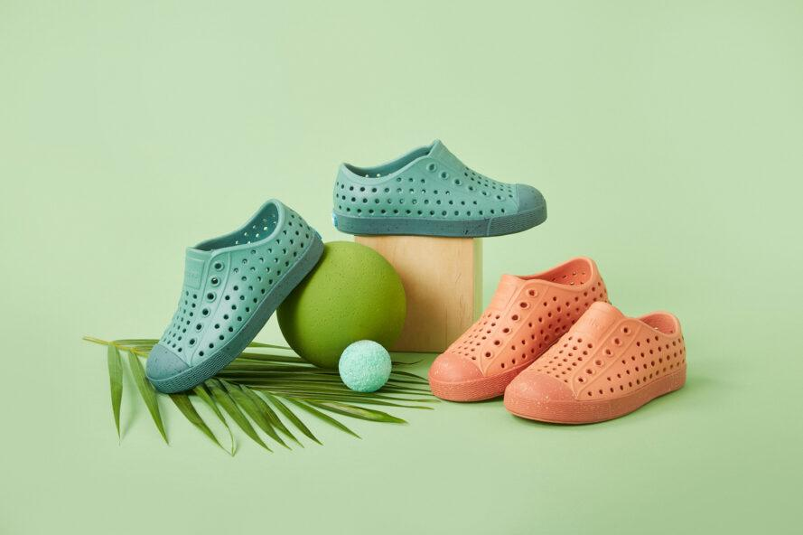 teal and orange perforated sneakers for kids on green background