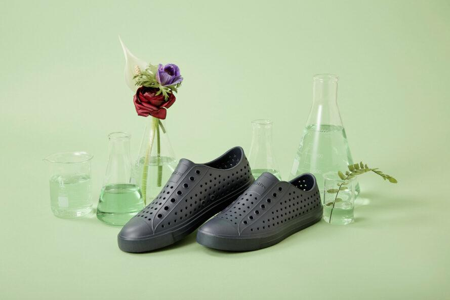 black perforated sneakers on green background
