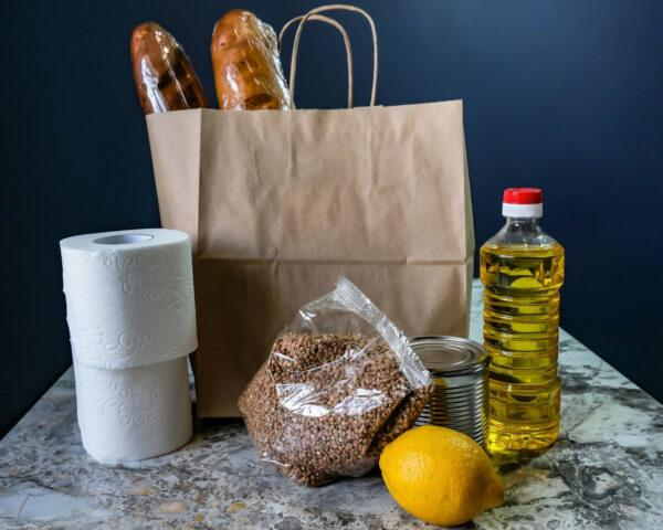 paper bag with loaves of bread, toilet paper, lemon and vegetable oil
