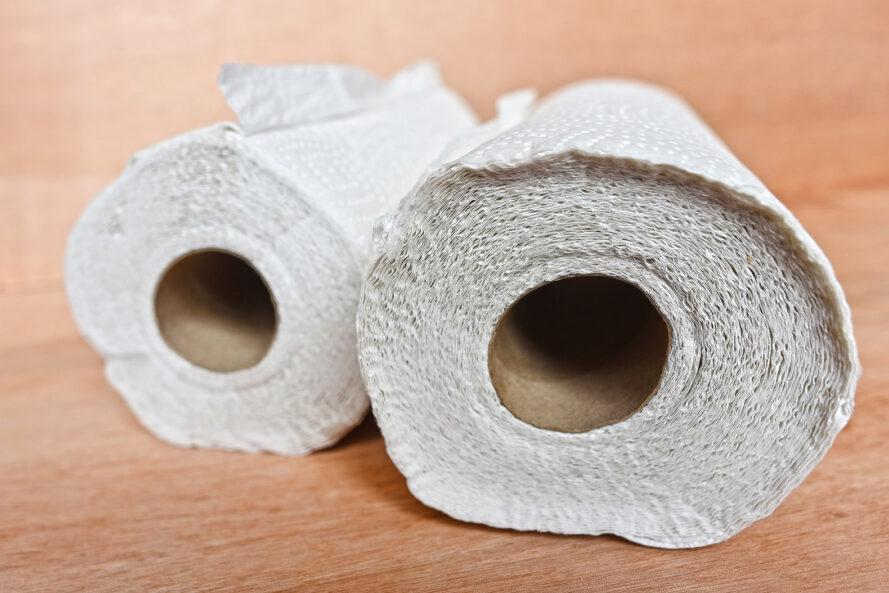 two rolls of paper towels on a wood surface